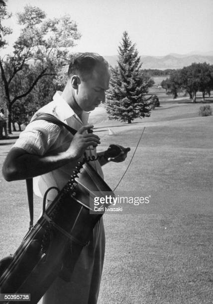 One of Dwight D Eisenhower's secret service men in sports clothes carrying golf bag as he prepares to follow Ike's game