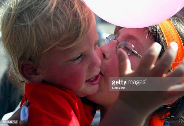 One of five Young Jewish settler girls kisses her baby brother as they are given a heros welcome on their return from Israeli detention on June 20 in...