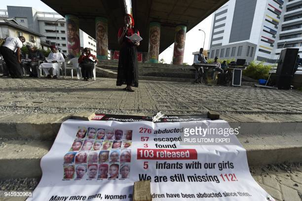 One of founders Bring Back Our Girls movement Aisha Oyebode speaks behind banner with photographs of missing girls to press for the release of the...