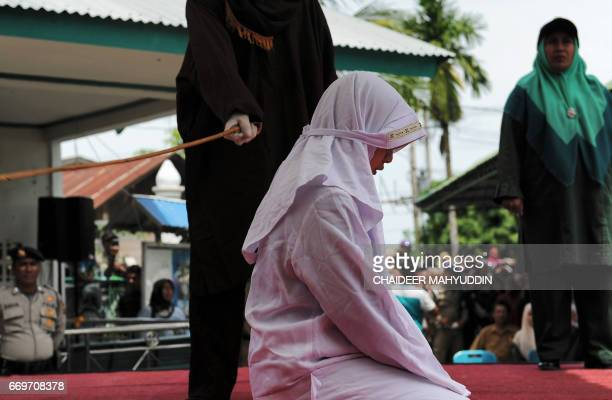 TOPSHOT One of four Acehnese teen gets whipped for spending time in close proximity with her boyfriend who is not her husband which is against Sharia...