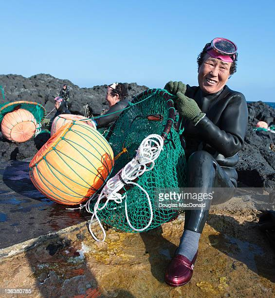 One of Jeju's grandma divers flashes a smile while emptying her nets of shellfish.