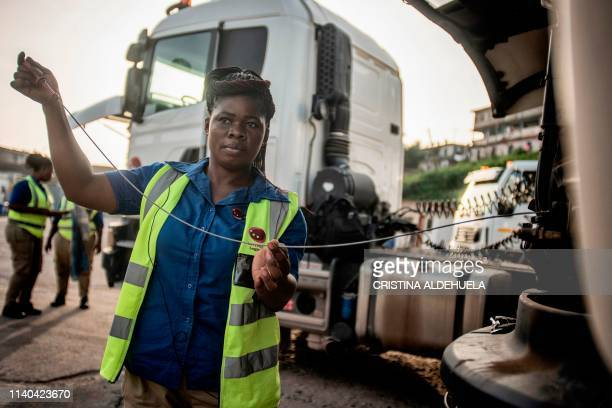 One of Ladybird Logistics' 21 female truck drivers checks her truck's oil level before the start of the workday in Takoradi, western Ghana, on April...