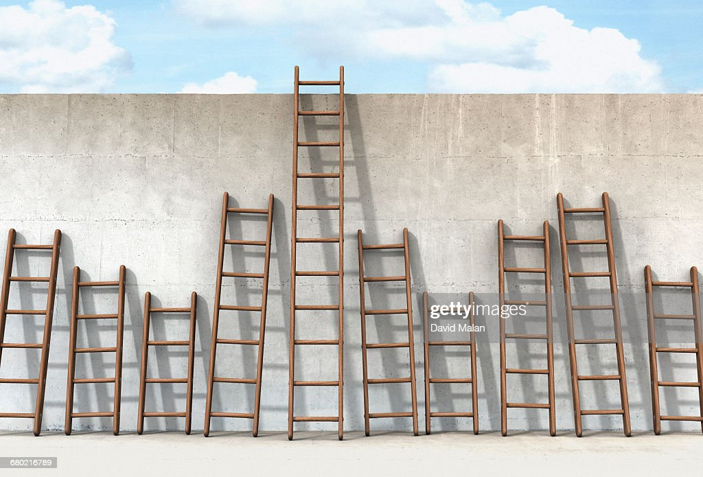 one of many ladders reaching the top of a wall : Stock Photo