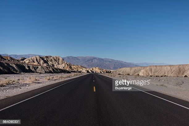 One of many long straight black roads in California Death Valley