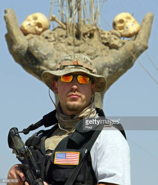 One of Paul Bremer's private security guards stands in front of a monument built at site where a mass grave of Saddam Hussein's regime victims was...