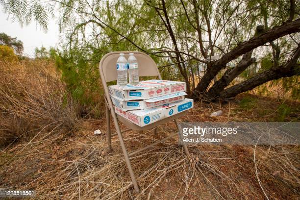 One of seven metal chairs with boxes full of pizza and water bottles sits under a tree at the property where seven people were shot to death over...