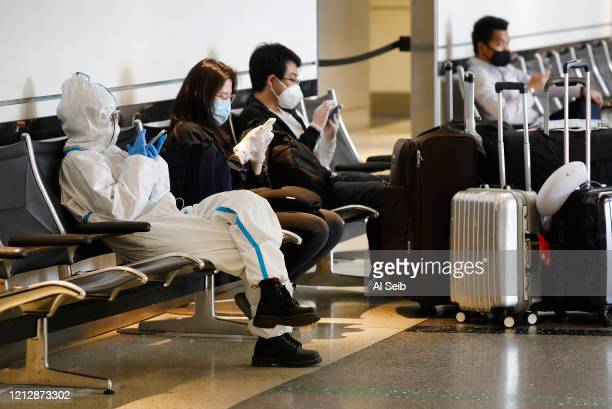 One of several students returning home to China after studying in the U.S. Wears a protective suit while waiting for a flight at the Tom Bradley...