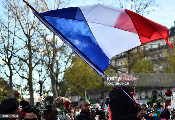 One of several women holding flags of France the EU and Democratic Republic of the Congo walks to lay a rose at Place de la Republique in Paris on...