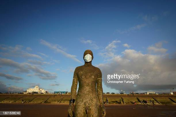 One of the 100 life-size body cast statues of 'Another Place' at Crosby beach, created by the artist Sir Antony Gormley wears a Covid-19, coronavirus...