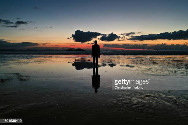 One of the 100 life-size body cast statues of 'Another Place' created by the artist Sir Antony Gormley looks out over the Mersey Estuary at sunset on...