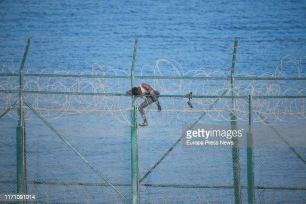 One of the 153 migrants who have jumped the fence of Ceuta at the first incursion of the year is seen on the top of the fence on August 30, 2019 in...