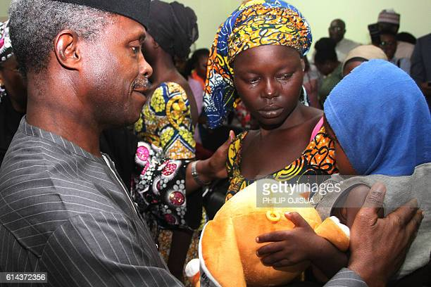 One of the 21 freed Chibok girls cries while holding her baby as Nigerian Vice President Yemi Osinbajo looks on at his office in Abuja on October 13...