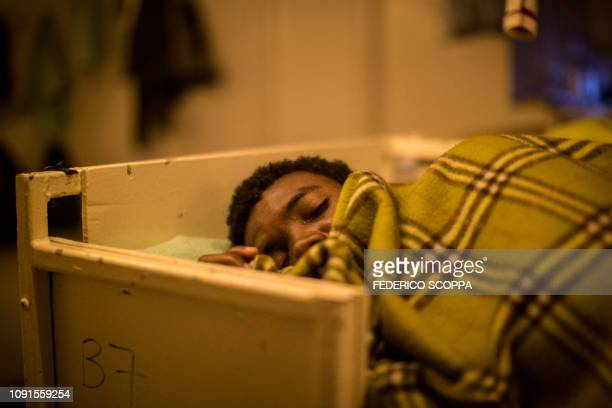 TOPSHOT One of the 47 rescued migrants aboard the Dutchflagged Sea Watch 3 NGO vessel sleeps on a bunk bed in the recovery room late on January 30...