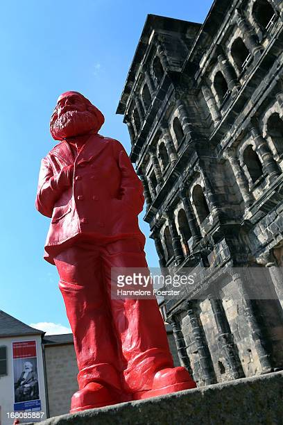 One of the 500 one meter tall statues of German political thinker Karl Marx in front of the Porta Nigra on display on May 5 2013 in Trier Germany The...