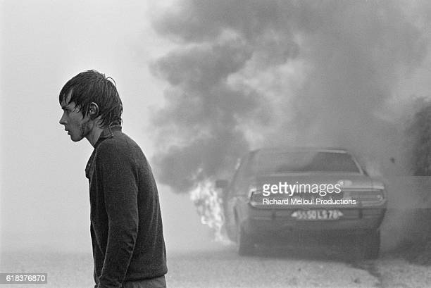 One of the 60000 European antinuclear activists protesting against the breeder reactor at CreysMalville walks past a burning automobile During the...