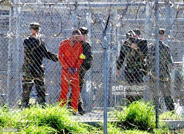 One of the 80 Al-Qaeda and Taliban detainees wearing an orange jump suit can be seen in his cell at Camp X-Ray surrounded by heavy security at the...