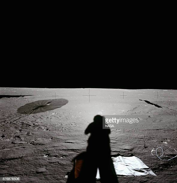 One of the Apollo 12 astronauts casts a shadow while taking a photograph on the surface of the Moon The brightening around the astronaut's shadowed...