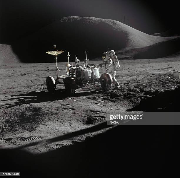 One of the Apollo 15 astronauts stands next to a lunar rover a fourwheeled vehicle used to travel across the surface of the Moon
