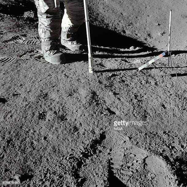 One of the Apollo 15 astronauts uses a thin metal pole to get a core sample on the surface of the Moon