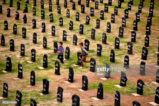 One of the cemeteries of the city, where the unidentified bodies of the 5,000 victims of the chemical attack of Halabja are buried; a black flag with...