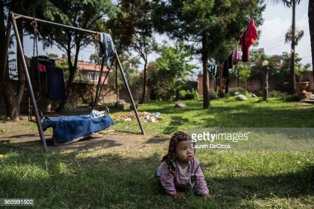 One of the children living with their mother at Casa Nepal a safe house for victims of genderbased violence crawl through the garden on May 8 2018 in...