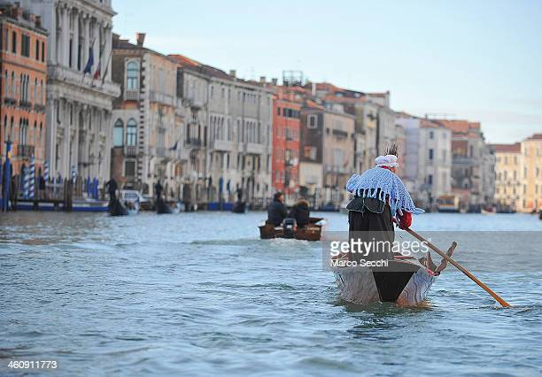One of the costumed participants races along the Grand Canal for the Befana Regatta on January 6 2014 in Venice Italy In Italian folklore Befana is...