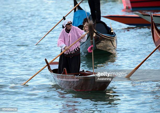 One of the costumed participants races along the Grand Canal for the 'Befana' Regatta on January 6 2014 in Venice Italy In Italian folklore Befana is...