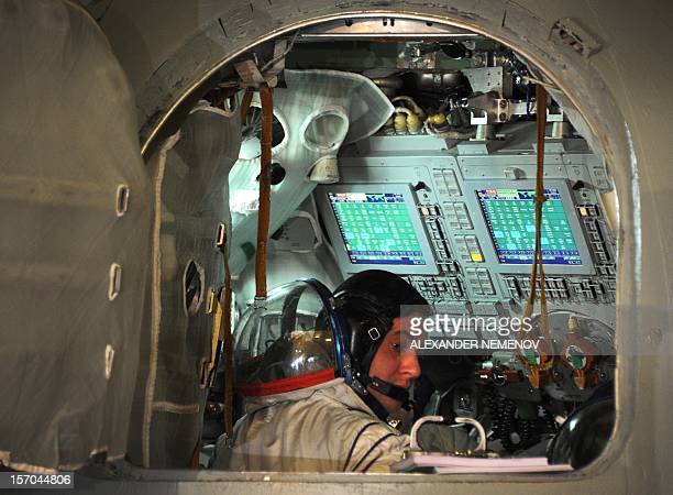 One of the crew members of the next expedition to the International Space Station Russian cosmonaut Roman Romanenko sits inside of a mockup of a...