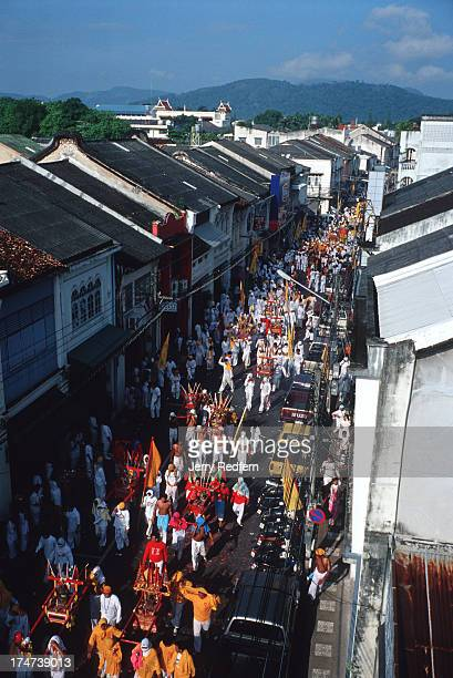 One of the daily parades of the Phuket Vegetarian Festival snakes down an oldtown street in Phuket town Much of the parade is devoted to men and...