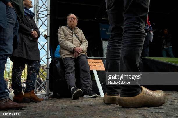 One of the demonstrators sitting next to the podium where the leaders of the basic income demonstration speak on October 26 2019 in Amsterdam...