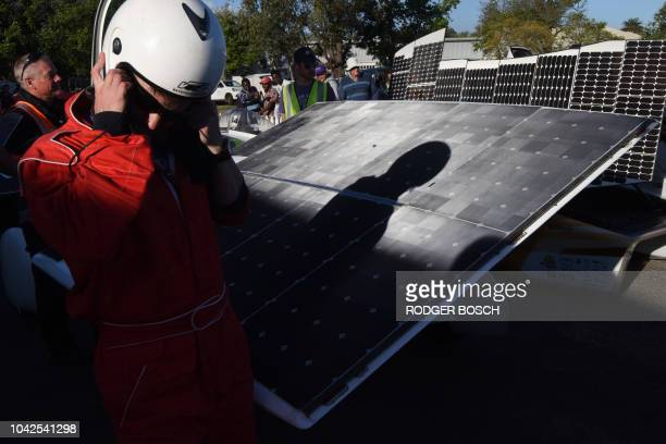 One of the drivers walk past the solar array of two of the cars taking part in Day 7 of the Sasol Solar Challenge on September 28 in Swellendam South...