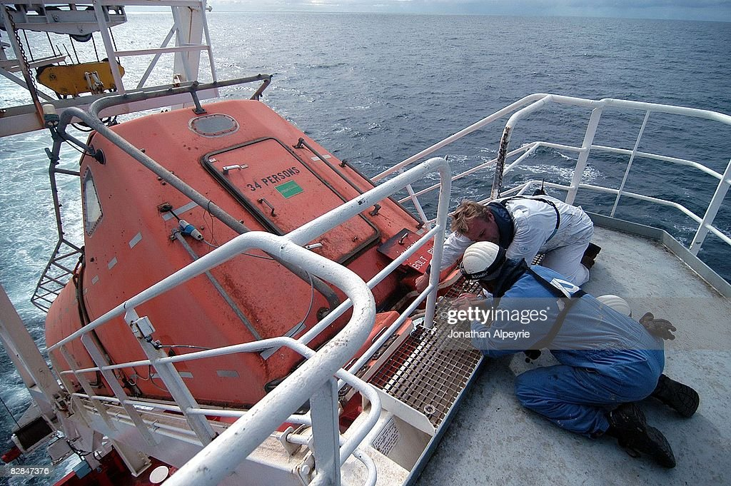 One of the Dutch officers is showing how the emergency boat works to one of the Filipino seaman, on July 20, 2008, in France. If the tanker sinks all crew members are supposed to enter this exit boat, then release it into the ocean.