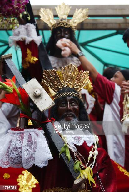 One of the faithful rubs a Black Jesus icon outside the Saint John the Baptist Church during the annual procession of the Feast of the Black Nazarene...
