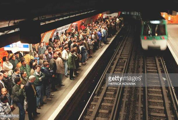 One of the few running metro trains enters a station as a crowd of Parisians waits on the platform as a strike by bus subway and rail services...