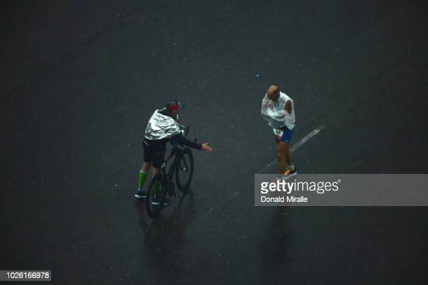 One of the final competitors to finish 79 yearold Pierre Bertolino of France walks in the rain while another triathlete reaches out during the Isuzu...