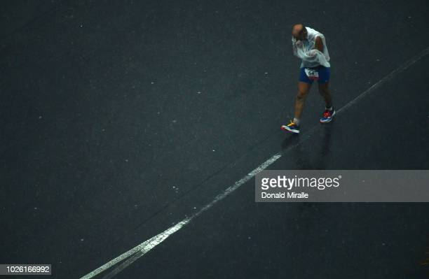One of the final competitors to finish 79 yearold Pierre Bertolino of France walks in the rain during the Isuzu IRONMAN 703 World Championship Men in...