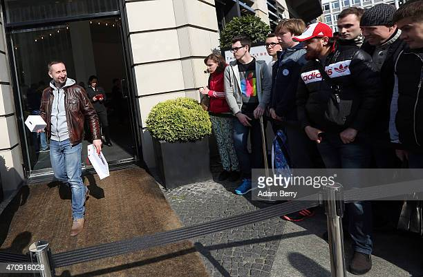 One of the first Apple fans to have successfully purchased the new Apple Watch at The Corner luxury shop greets others waiting in line to do so as...