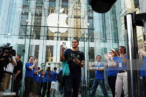 One of the first customers in line at the flagship Apple Store on Fifth Avenue displays his new iPhone 4 which went on sale this morning on June 24...