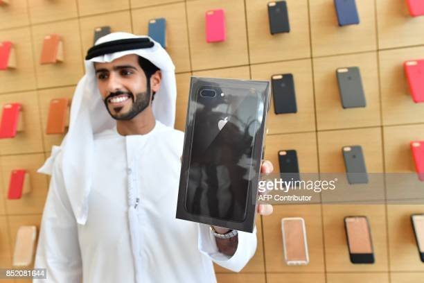 One of the first customers to buy the new Apple iPhone 8 poses at Dubai Mall Apple Store in Dubai on September 23 2017 The new Apple iPhone 8 and 8...