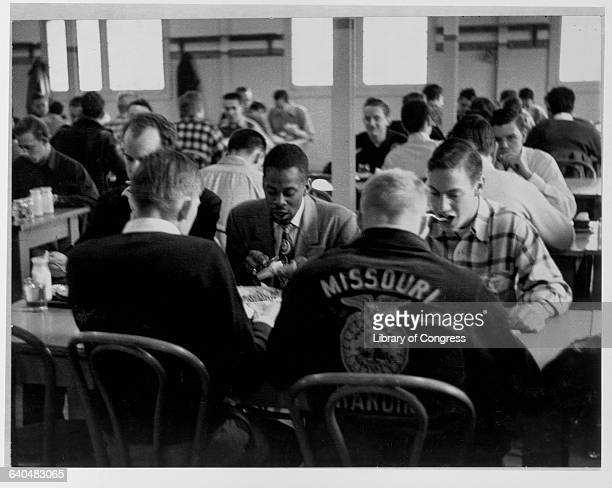One of the first ten African American students admitted to the University of Missouri eats in the dining hall alongside Caucasion students following...