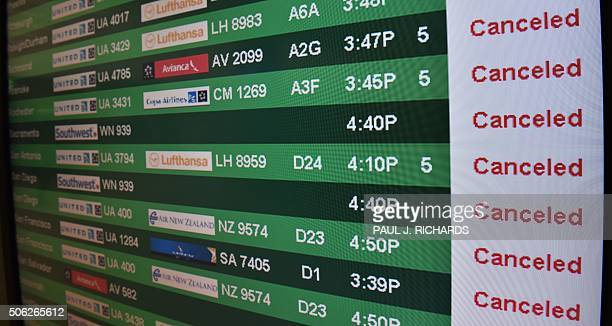 One of the flight status board for arrivals and departures is viewed at Dulles International Airport just outside Washington DC January 22 2016 in...