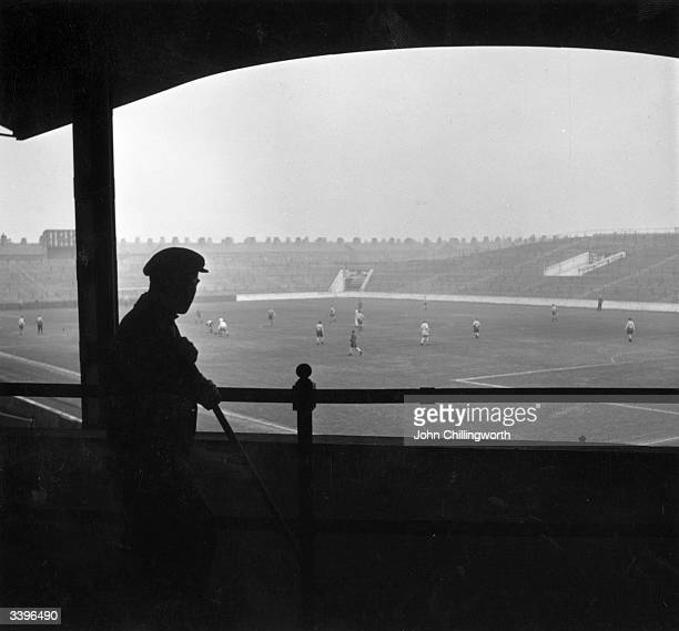 One of the groundstaff watches the players of Manchester City Football Club during a training session at Maine Road Original publication Picture Post...