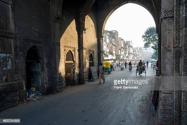 One of the historic City Gates of the old city with pedestrians and a cycle rikshaw
