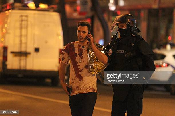 One of the injured victim escorted by the police in front Bataclan concert hall. At least 129 people have been killed and over 200 injured, 80 of...
