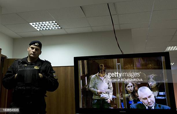 One of the jailed members of the allgirl punk band Pussy Riot Yekaterina Samutsevich is seen on a seen as she speaks from a glasswalled cage in a...