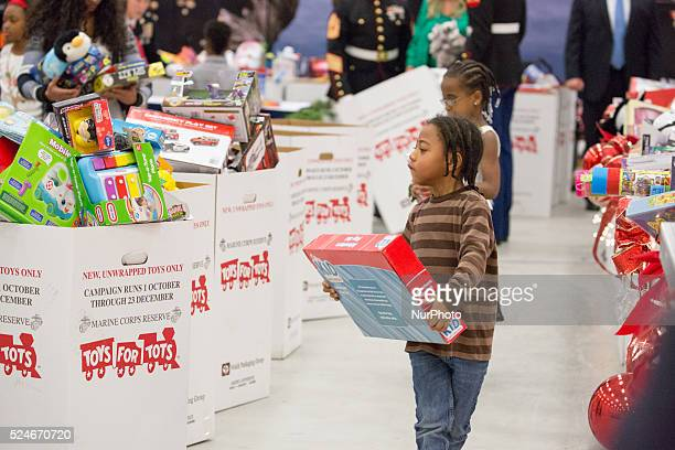 C — One of the kids sorts toys with other volunteers at the Joint Base AnacostiaBolling for the Marine Corps Reserve Toys for Tots Campaign