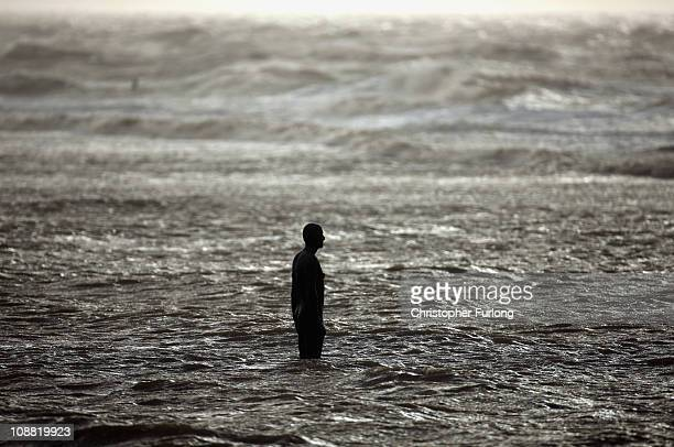 One of the lifesize body cast statues of 'Another Place' created by the artist Antony Gormley is lashed by windswept waves on Crosby Beach as the...