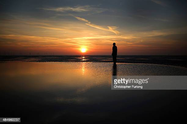 One of the life-size body cast statues of 'Another Place' created by the artist Antony Gormley looks out over the Mersey Estuary at sunset at Crosby...
