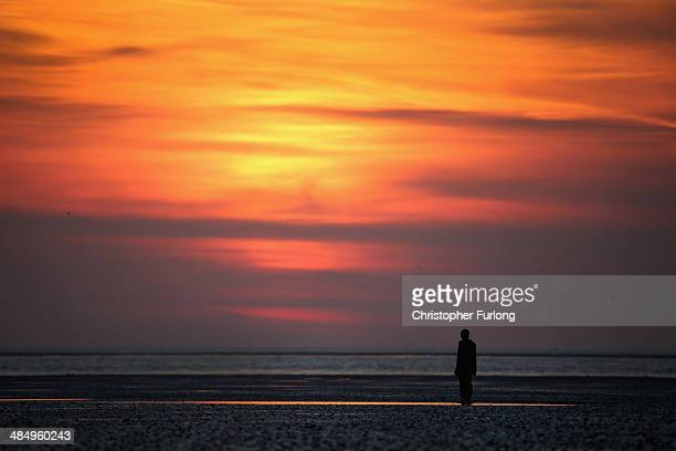 One of the lifesize body cast statues of 'Another Place' created by the artist Antony Gormley looks out over the Mersey Estuary at sunset at Crosby...