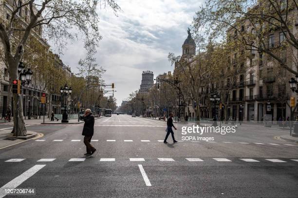 """One of the main arteries of the city, the popular Passeig de Gràcia is seen almost deserted. After the Spanish Government decreed a """"state of..."""